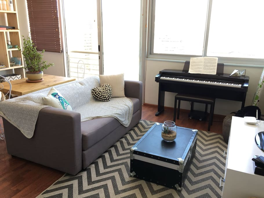 The living room has a TV, sleeper couch and piano.