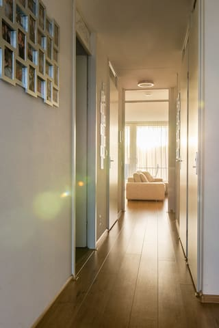 Hall from entrance door to living room and glass doors to the balcony