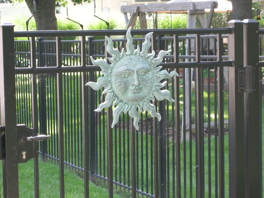 The entrance gate, to the south of the Residence opens onto a well lighted walkway.  The gate is clearly marked by a sun face you see in this picture.