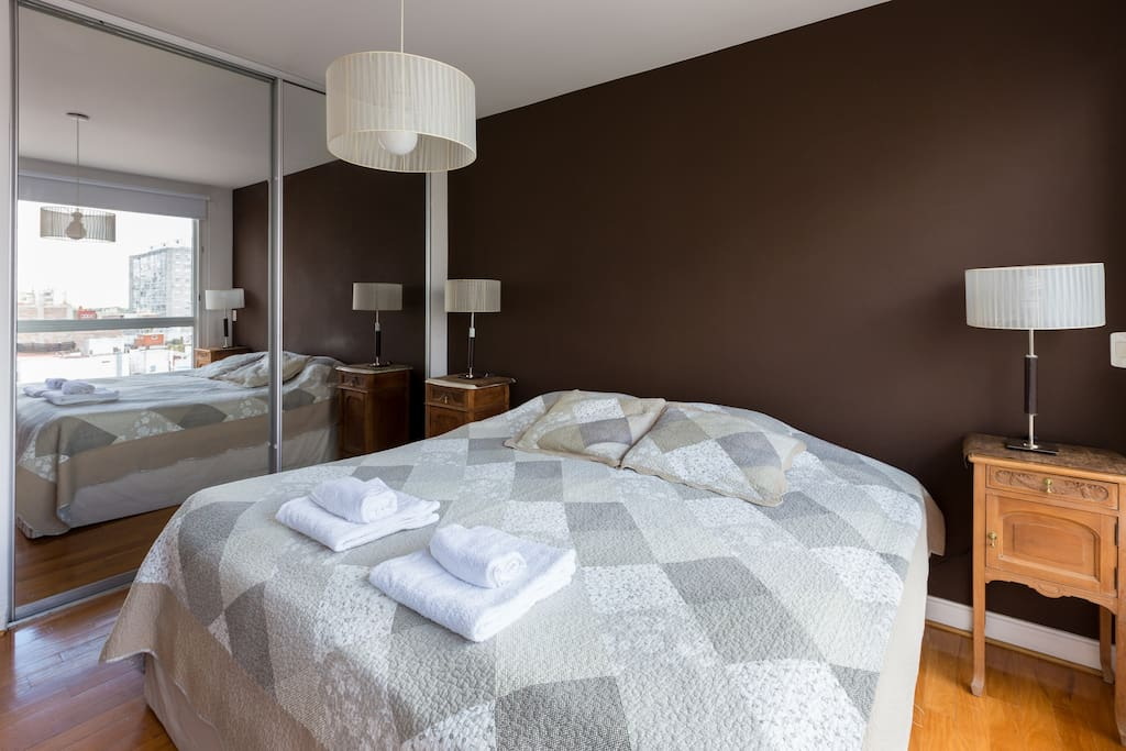 The master bedroom has a king-sized bed, floor-to-ceiling mirrored closets and design bedside lamps and tables