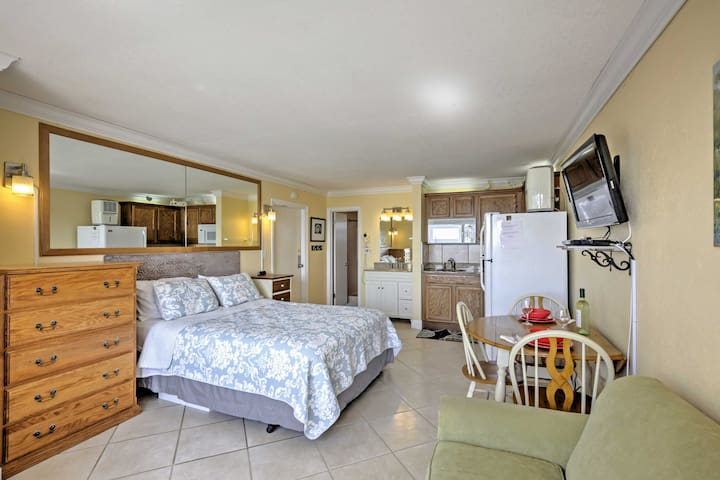 Sunlight illuminates the open living area featuring a queen-sized bed, flat-screen cable TV, and cozy love seat.