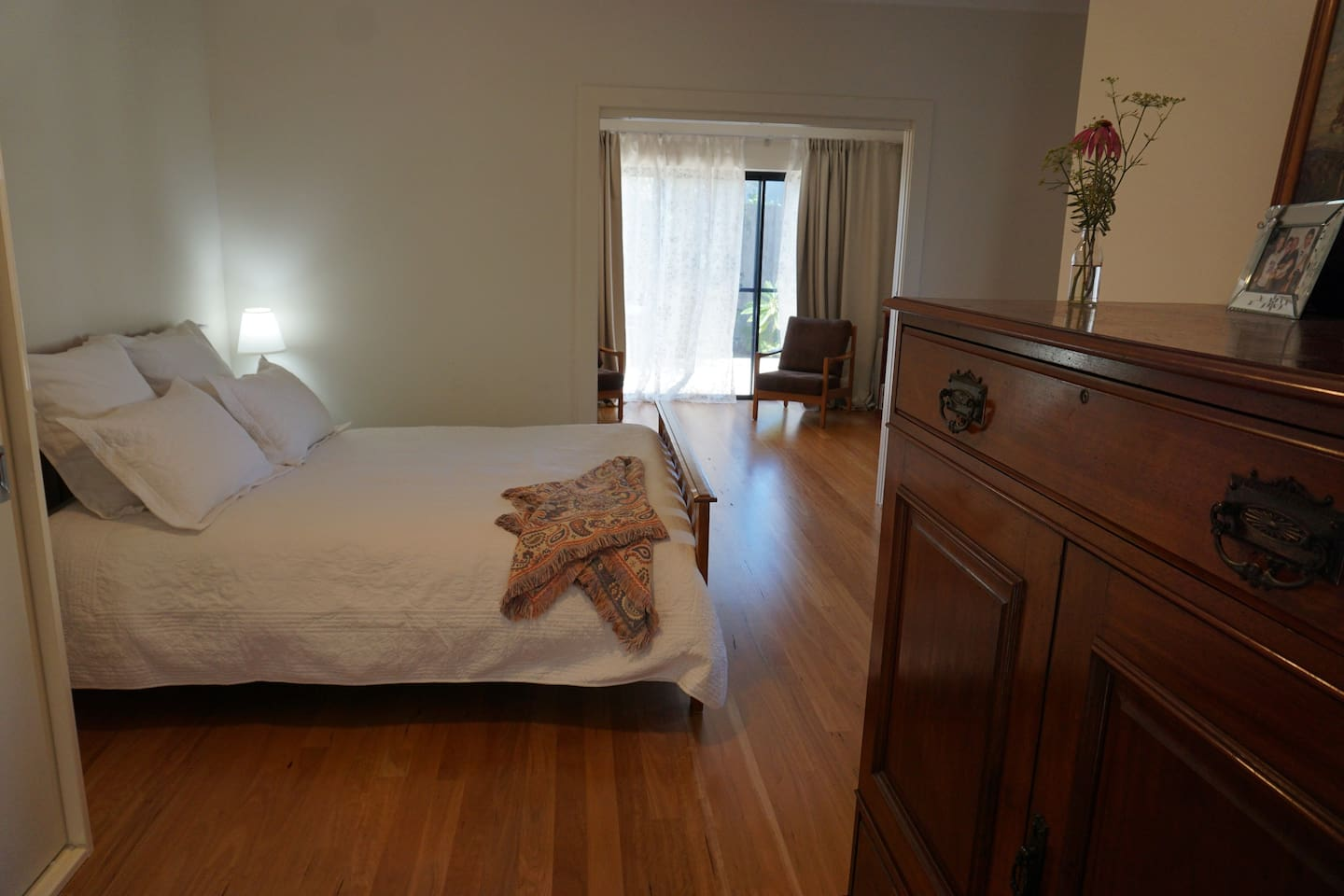 Spacious bedroom with queen bed, pocket sliding doors open to the lounge room.