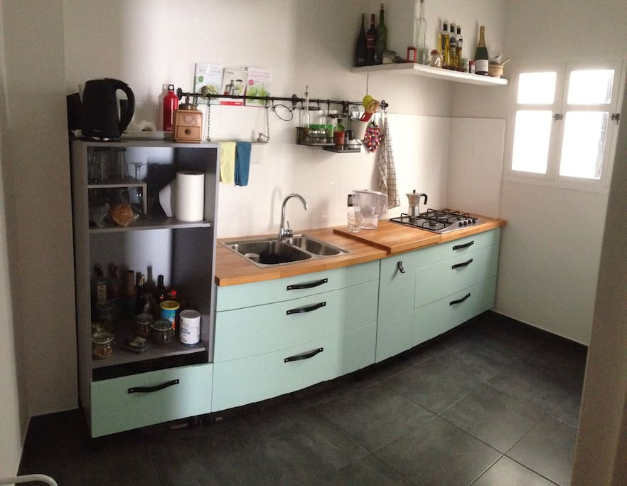The kitchen also has a fridge on the right side.