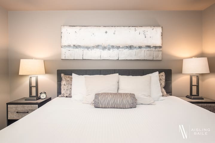The master bedroom features a king sized bed with premium hotel linens.