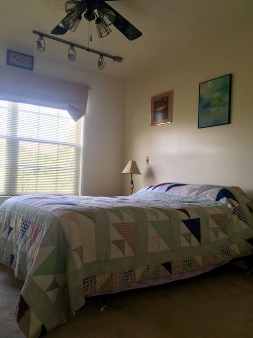 There's a sunny window in the bedroom, along with a ceiling fan.