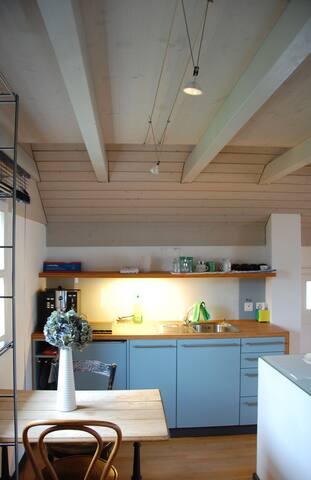 Kleine Kaffeküche mit Kühlschrank, 2 Herdplatten und Kaffeemaschine.