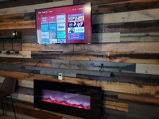 50 inch Flat Screen Roku Smart TV including NETFLIX.  The fireplace has heat and color settings for mood lighting.  The wall is reclaimed wood.