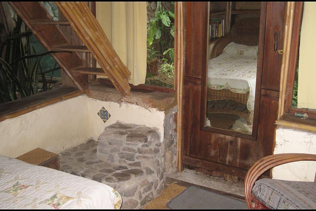 Living area with ladder/steps to bed on platform above