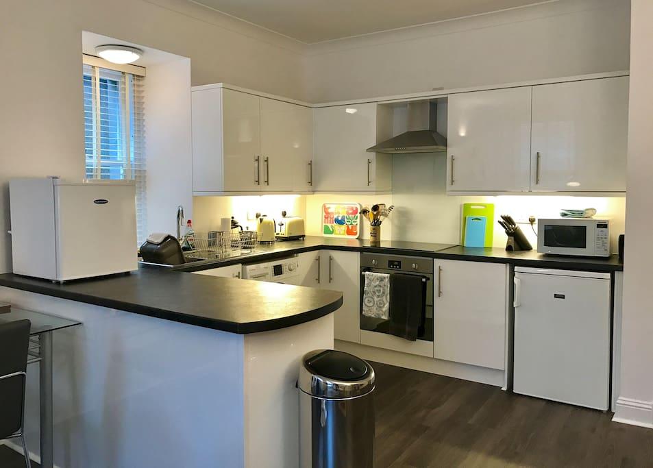 Kitchen with washer/drier, fridge, microwave & small freezer.
