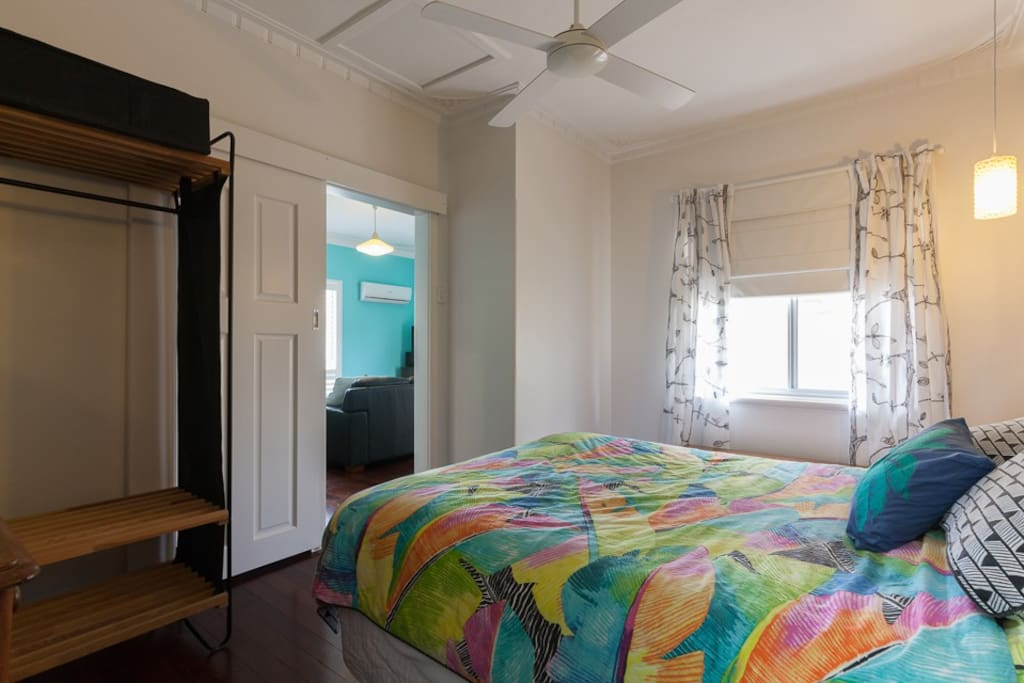 The main bedroom has a luxurious Queen size bed and an overhead fan.