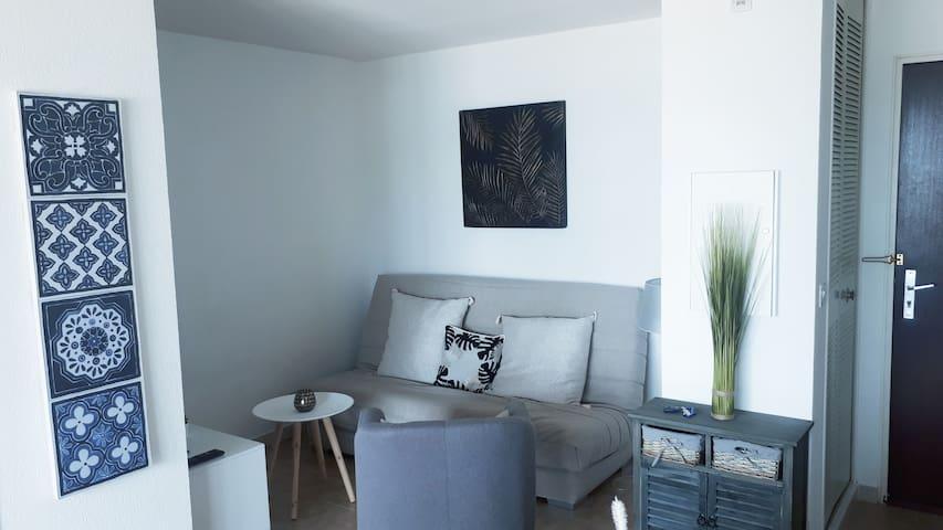 Coin salon avec écran  plat et  canapé  lit dépliable matelaq bultex