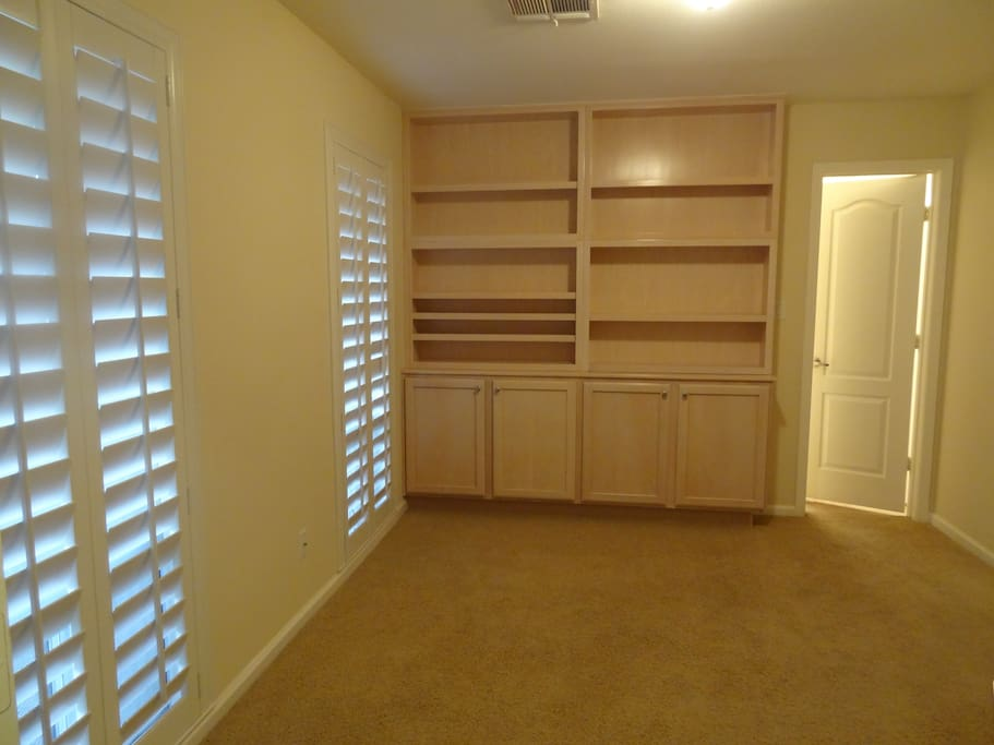 2nd bedroom with built-in bookcase, shelving, cabinets