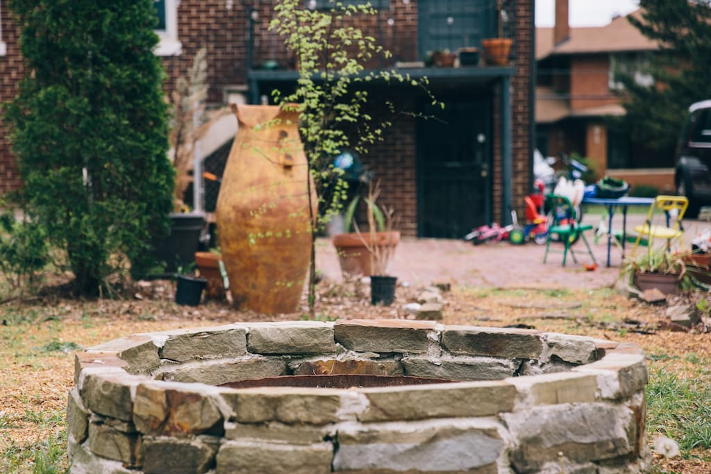 Overlooking fire pit towards daylight basement apartment entrance
