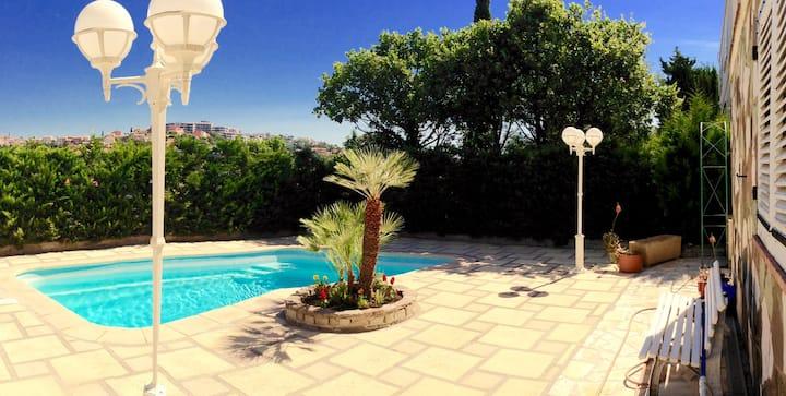 Logement spacieux pouvant accueillir jusqu'à 6 personnes -  Rez-de-jardin de villa avec piscine.