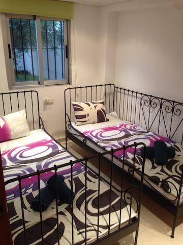 Habitación doble con camas de 90 y mosquitera en la ventana