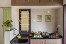 The kitchen counter with a stove, essential vessels and basic things to cook.