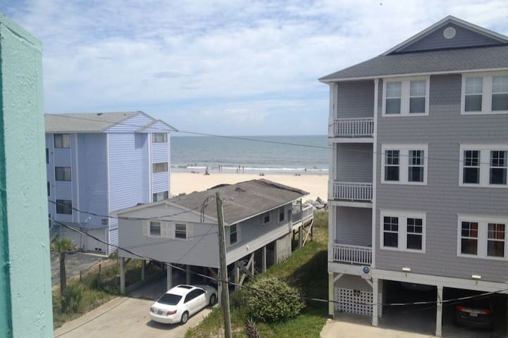 Enjoy the ocean view from the porch.  (Note: this is the view from the porch of the condo overlooking homes to the beach.)