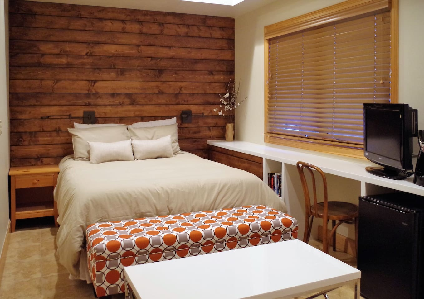 Queen size bed with storage bench and coffee table at end, reading lamps, laptop area, books, tv, and mini-fridge