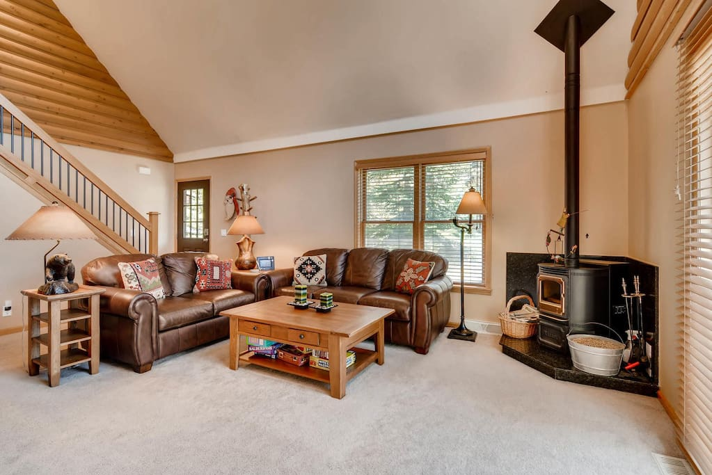 The living room offers seating on a leather couch and matching love seat