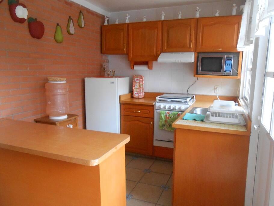 Cocina con refrigerador,estufa, licuadora, sandwichera y horno de microondas.