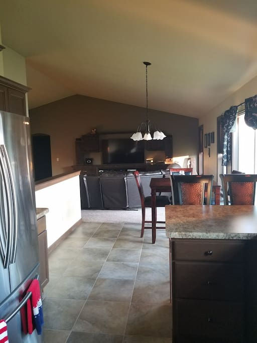 """open concept kitchen, dining, living room. Large built in entertainment center with 70"""" centerpiece!!!"""