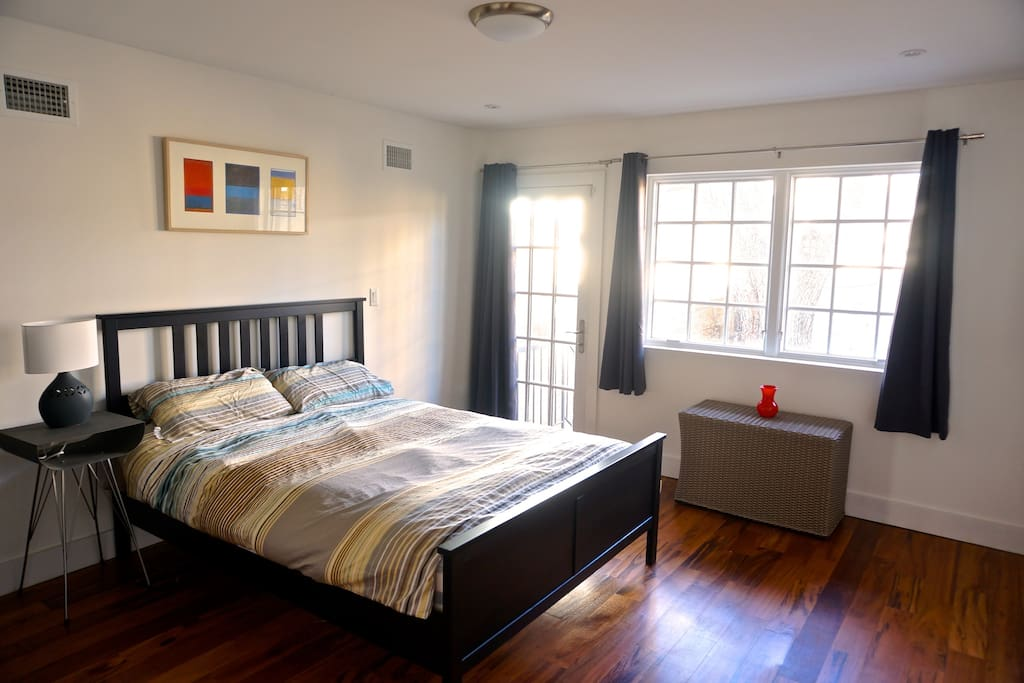 Bedroom with access to private backyard, en suite bathroom and queen bed.