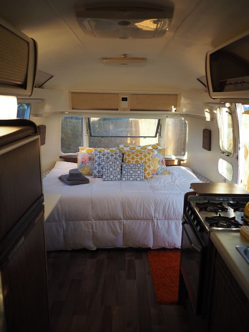 Full bed in the front with quality linens and assorted pillows.