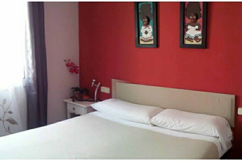 Habitación con cama de matrimonio, escritorio, TV dvd y perchero.