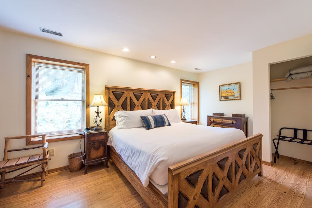 Riverside bedroom has a big beautiful wood and leather bed with