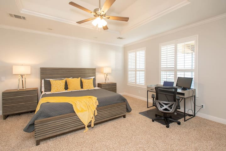 Spacious master bedroom with desk and office chair in case you need to work remotely.  Shutters throughout the house with views of lake from the desk.