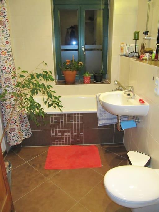 das Bad mit Wanne und großem Spiegel