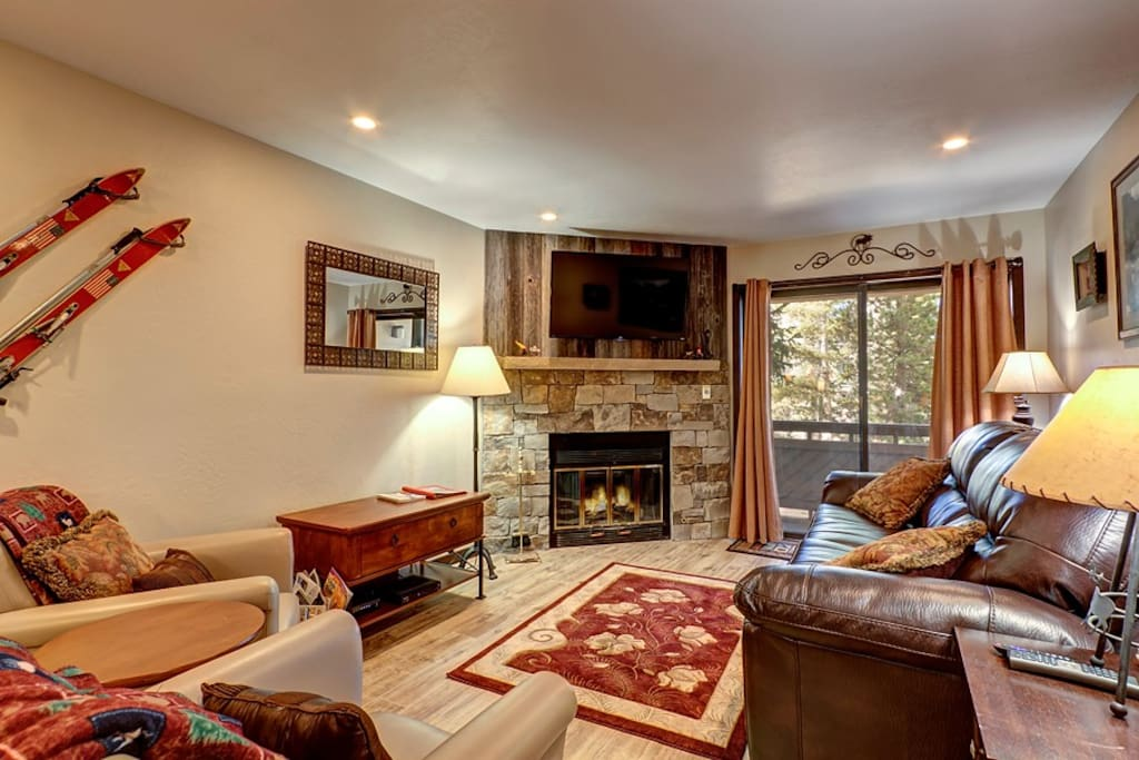 """The living room features a gas fireplace, 48"""" TV, and access to balcony."""