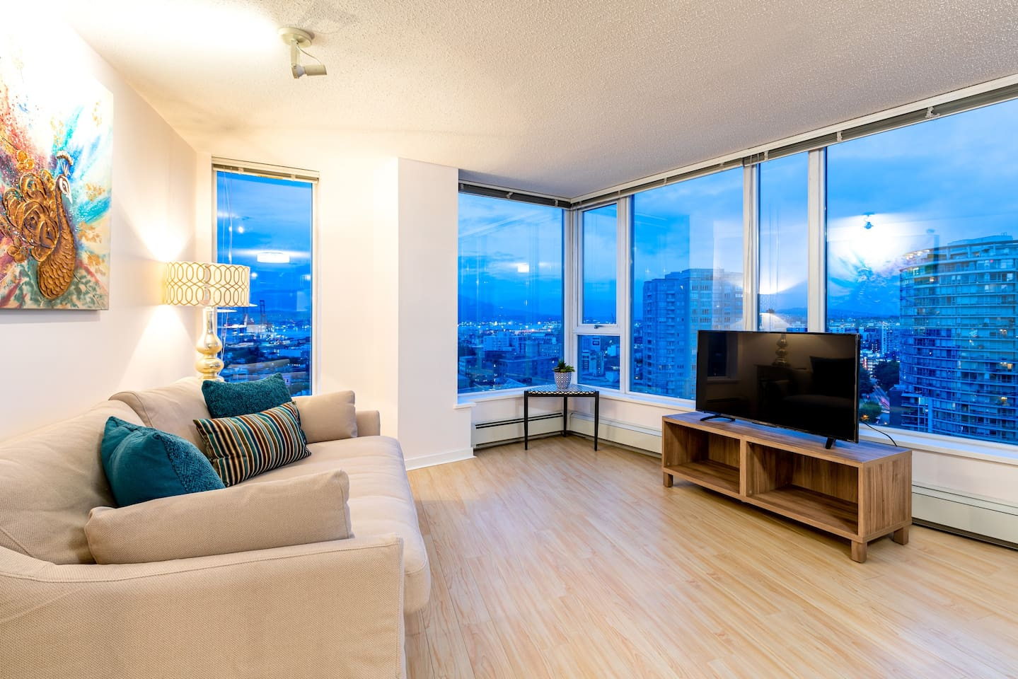 Main living space with open-concept layout, queen size sofa bed, flat screen TV with Netflix and large windows to enjoy views of Downtown Vancouver