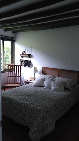 Alcabo Camelias (alcoba principal en el primer piso de la casa, con una cama doble y baño adjunto)