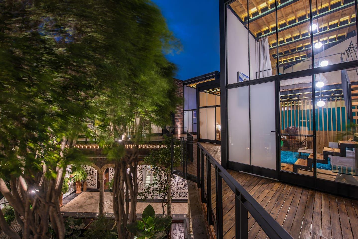 La habitación en dos plantas, con pisos de madera, posee una amplia vista al jardín, y cuenta con cortinas dobles.