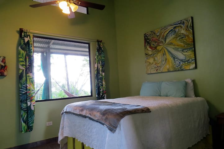 Master suite with queen ortho mattress, ceiling fan, large windows with mountain and tropical garden views