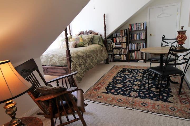 A lovely light airy upstairs room with a natural fiber / organic topped four poster queen size bed. A table for two, bookshelves with an interesting collection of books from many cultures, artwork including original photos and sculpture all make this a comfortable as well as unique room