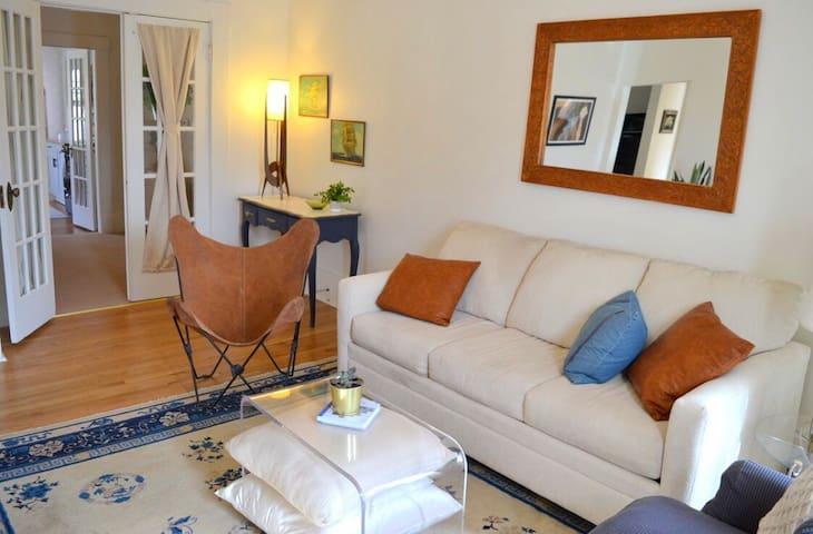 Living room, with work space (desk in corner).  Front doors open to main hall.
