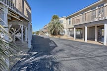 This view is from the entrance (the two-lane road and beach are behind the camera). Your unit is located in that back building on the right, bottom floor near the middle. Parking is available underneath.