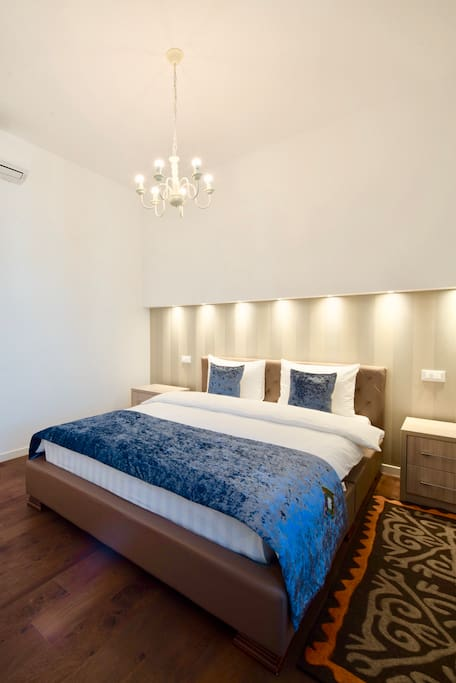 comfortable bedroom, with white linens, furniture from Italy, orthopedic mattress, decor in ethno style