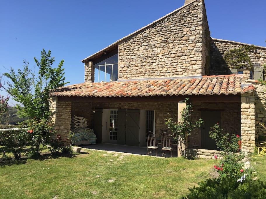 L'entrée de la maison depuis le jardin, en passant par la terrasse ombragée