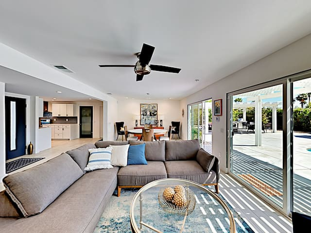 Contemporary style welcomes you into the open-concept living room, where sliding glass doors  overlook the shimmering pool.