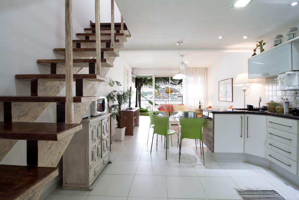 Vista geral do 1º andar, cozinha integrada com sala ao fundo privilegiando vivência sem amontoar. As suítes no 2º andar.