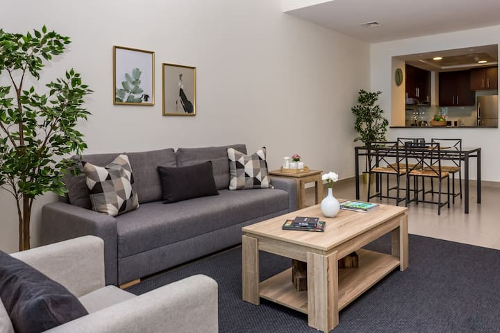 The living area of the apartment includes comfortable sofas, coffee table and flat TV for guests' entertainment