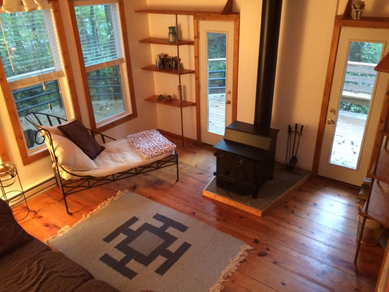 Living area with wood burning stove and access to deck