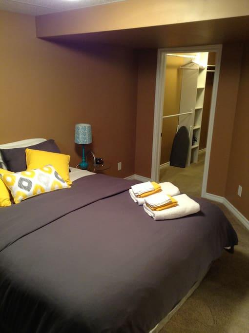 Lamp, alarm clock, large closet, iron and small ironing board.