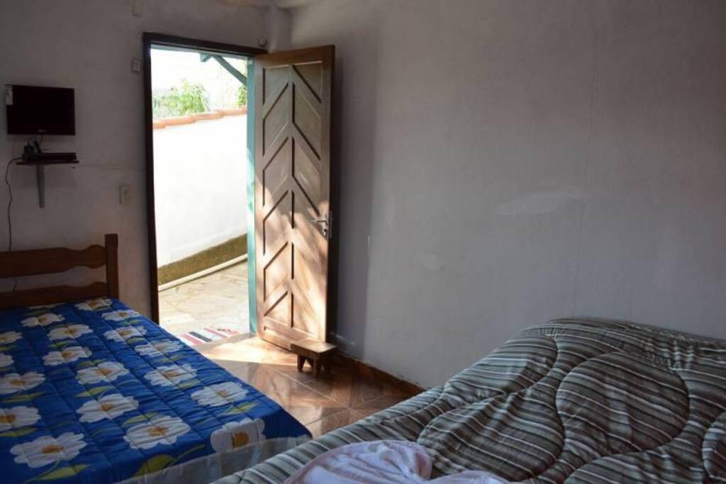 Quarto n°6, possui 1 cama de casal, 1 de solteiro, tv de led, banheiro, fica na parte de baixo perto do salão de café, ventilador.