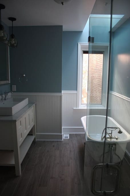 Upstairs bath with clawfoot tub below a skylight, glass enclosed shower, and separate toilet room.