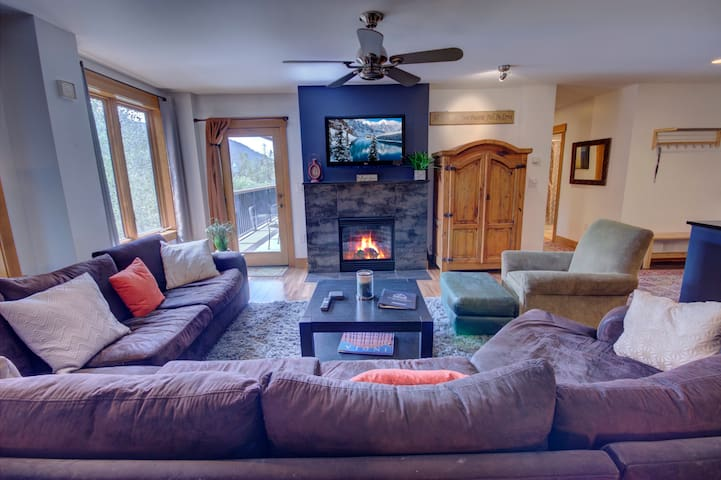 A living room with a TV and fireplace with a great view of the mountains