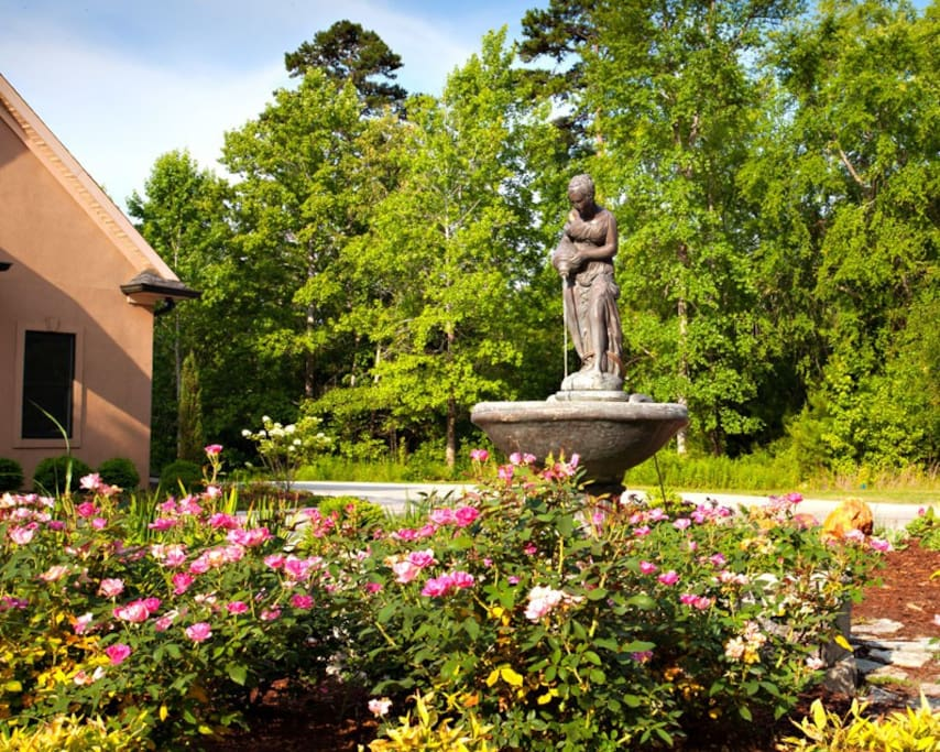 Lush landscaping, circular drive and decorative fountain adorn the front yard.